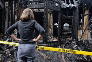 Woman standing in front of her home after fire damage
