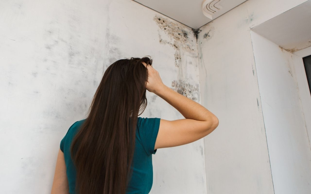 Woman looking at mold in confusion